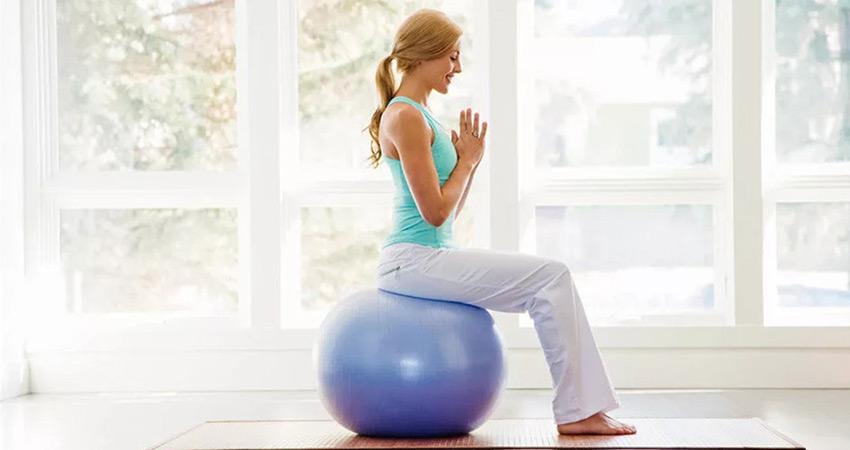 Девушка держит ровную осанку сидя на фитболе
