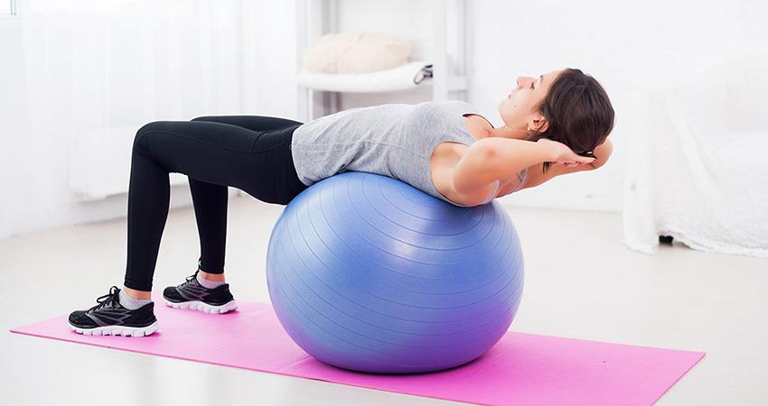 Девушка лежит спиной на фитболе