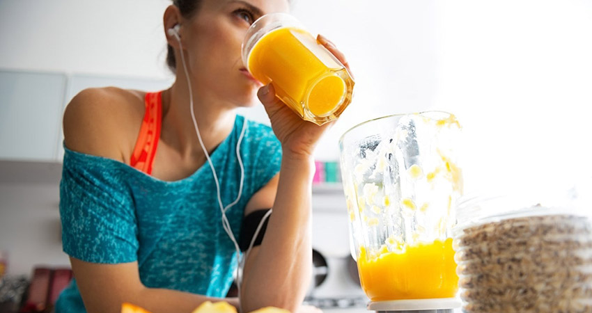 Девушка пьет сок во время тренировки
